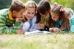 Kinderen lezen een boek op het gras